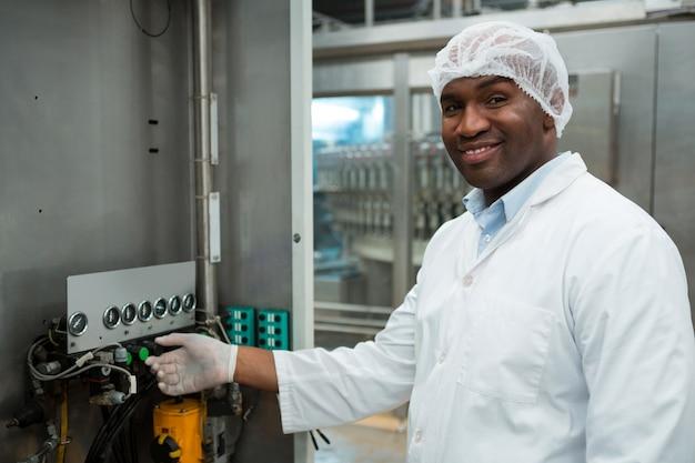 Zuversichtlich männliche arbeiter, die maschine in saftfabrik bedienen