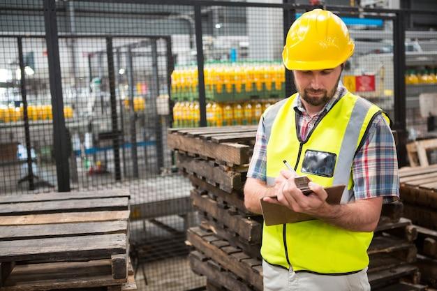 Zuversichtlich männlicher arbeiter, der über produkte bemerkt