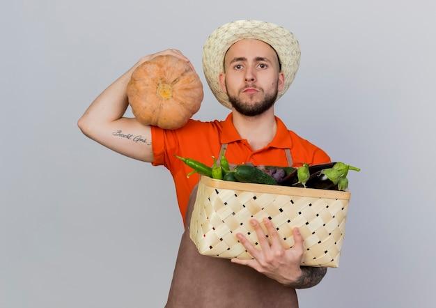 Zuversichtlich männlicher gärtner, der gartenhut trägt, hält kürbis und gemüsekorb
