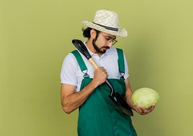 Zuversichtlich männlicher gärtner in optischen gläsern, die gartenhut tragen, hält spaten und schaut kohl an