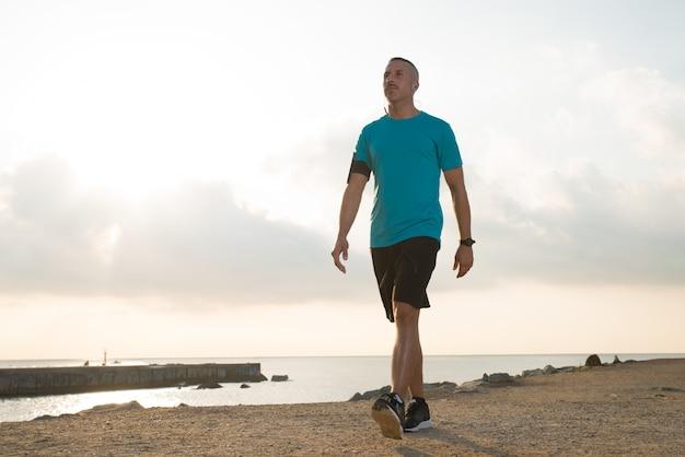 Zuversichtlich männlicher jogger, der nach dem laufen läuft