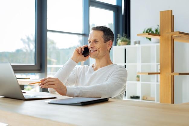 Zuversichtlich manager. glücklicher entzückter netter mann, der einen bleistift hält und auf den laptopbildschirm zeigt, während er am telefon spricht