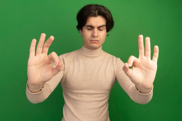 Zuversichtlich mit geschlossenen augen junger gutaussehender kerl, der meditationsgeste isoliert auf grüner wand macht
