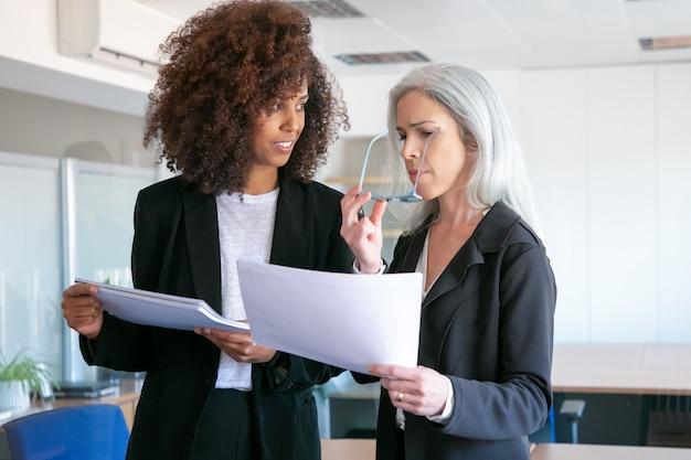 Zuversichtlich partnerinnen diskutieren dokument im büroraum. zwei attraktive, erfolgreich fokussierte geschäftsfrauen, die dokumentation studieren, berichten gemeinsam. teamwork-, geschäfts- und managementkonzept