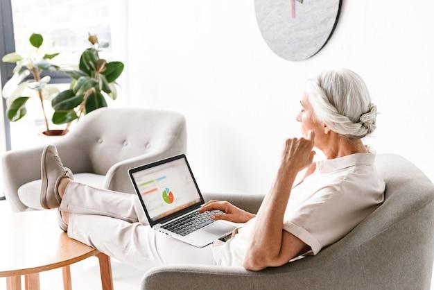 Zuversichtlich reife geschäftsfrau, die am laptop arbeitet