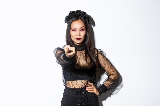 Zuversichtlich schöne asiatische frau in sexy hexenkostüm locken sie, erzählen sie näher kommen mit ausgestrecktem finger, feiern halloween und tragen gotisches kleid, über weißem hintergrund stehend.