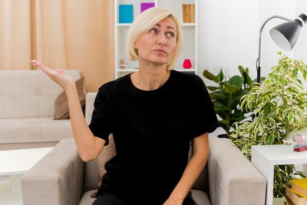 Zuversichtlich schöne blonde russische frau sitzt auf sessel, der hand offen hält und seite im wohnzimmer betrachtet
