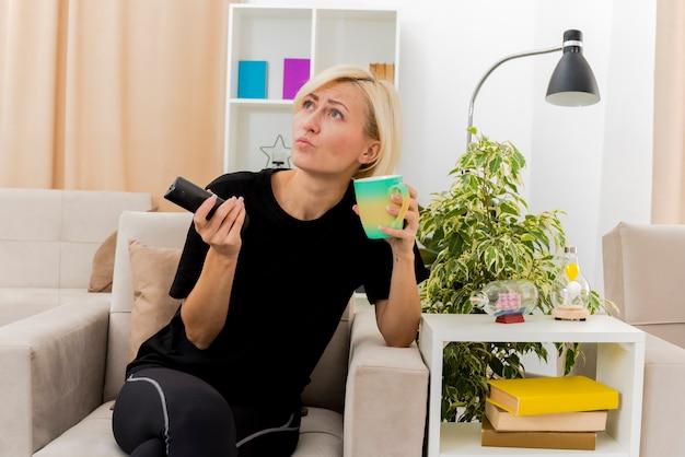Zuversichtlich schöne blonde russische frau sitzt auf sessel, der tasse und fernsehfernbedienung hält, die seite im wohnzimmer betrachten
