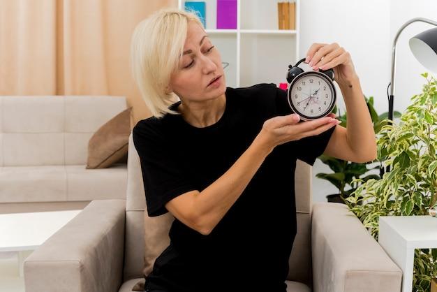 Zuversichtlich schöne blonde russische frau sitzt auf sessel, der wecker im wohnzimmer hält und betrachtet