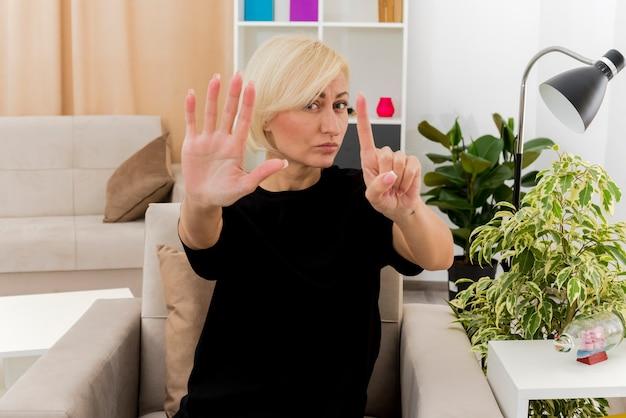 Zuversichtlich schöne blonde russische frau sitzt auf sessel und gestikuliert sechs mit den fingern