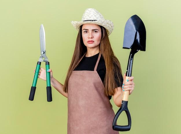 Zuversichtlich schöne gärtnerin in uniform mit gartenhut, die haarschneidemaschinen mit spaten lokalisiert auf olivgrünem hintergrund hält