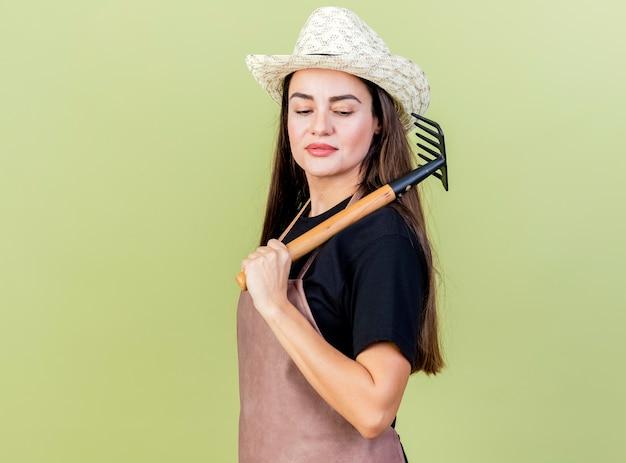 Zuversichtlich schöne gärtnerin in uniform mit gartenhut, die rechen auf schulter lokalisiert auf olivgrünem hintergrund setzt