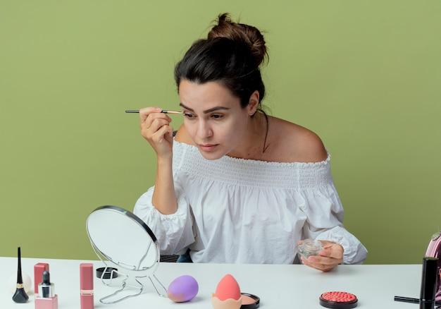 Zuversichtlich schönes mädchen sitzt am tisch mit make-up-werkzeugen schaut auf spiegel, der lidschatten mit make-up-pinsel auf grüner wand isoliert anwendet