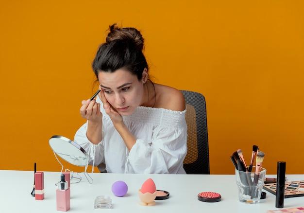 Zuversichtlich schönes mädchen sitzt am tisch mit make-up-werkzeugen schaut auf spiegel, der lidschatten mit make-up-pinsel auf orange wand isoliert anwendet