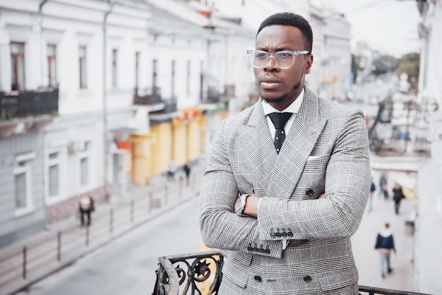 Zuversichtlich schwarzer geschäftsmann in einem stilvollen anzug, der auf büroblock steht und mit einem ernsten ausdruck schaut