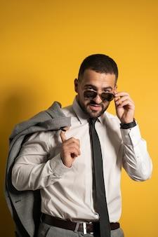 Zuversichtlich sexy senkender sonnenbrillengeschäftsmann gekleidet in der grauen suite, die posierend hält, seine jacke auf seiner schulter hängend sie hinter schaut isoliert auf gelber wand