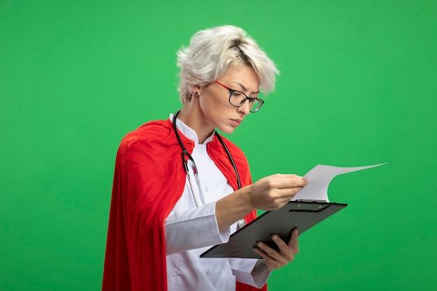 Zuversichtlich slawische superheldenfrau in der arztuniform mit rotem umhang und stethoskop in optischen gläsern, die zwischenablage lokalisiert auf grüner wand mit kopienraum halten und betrachten