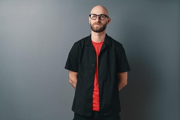 Zuversichtlich stilvoller junger bärtiger mann, der brille mit schwarzem rahmen trägt und im studio o grau aufwirft.