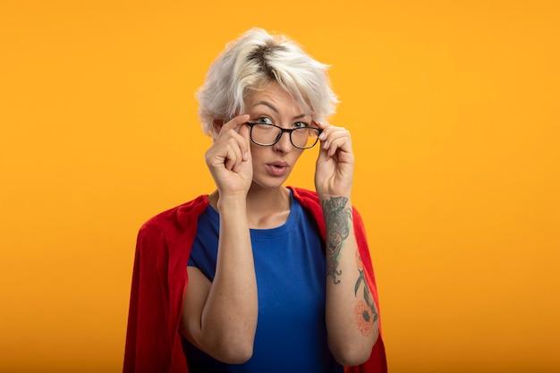 Zuversichtlich superfrau mit rotem umhang in optischen gläsern schaut vorne isoliert auf orange wand