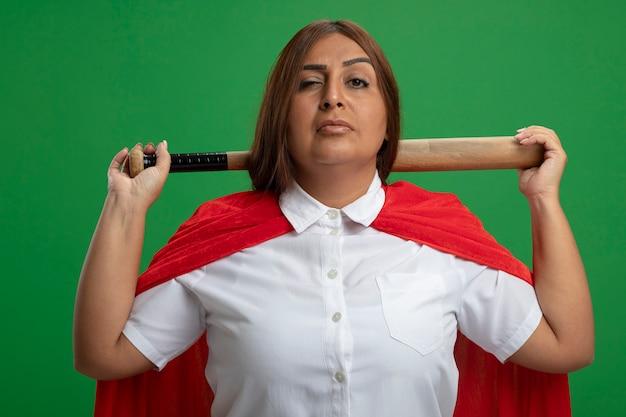 Zuversichtlich superheldenfrau mittleren alters, die baseballschläger hinter hals lokalisiert auf grün isoliert