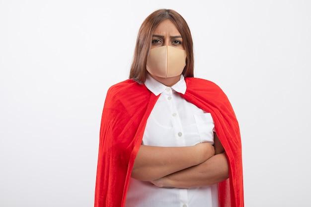 Zuversichtlich superheldenfrau mittleren alters, die medizinische maske trägt, die hände lokalisiert auf weiß kreuzt