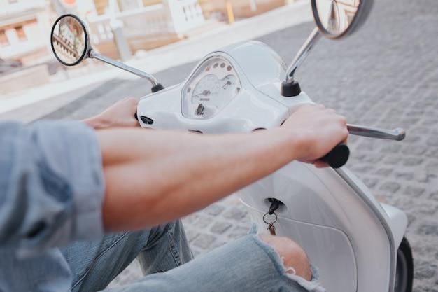 Zuversichtlich und attraktiver junger mann sitzt auf motorrad
