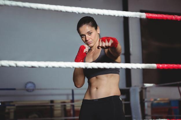 Zuversichtlich weiblicher boxer, der boxhaltung durchführt