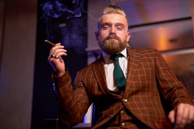 Zuversichtlich wohlhabender kaukasischer mann mit bart im formellen stilvollen anzug sitzen rauchende zigarre