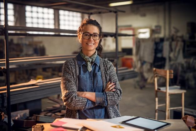 Zuversichtlich zufrieden lächelnde professionelle architektin posiert mit gekreuzten händen mit notizen, tablette und linealen auf dem tisch in der stoffstelle.
