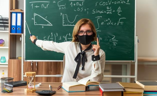 Zuversichtliche junge lehrerin mit brille und medizinischer maske sitzt am tisch mit schulwerkzeugpunkten an der tafel mit zeigerstock im klassenzimmer