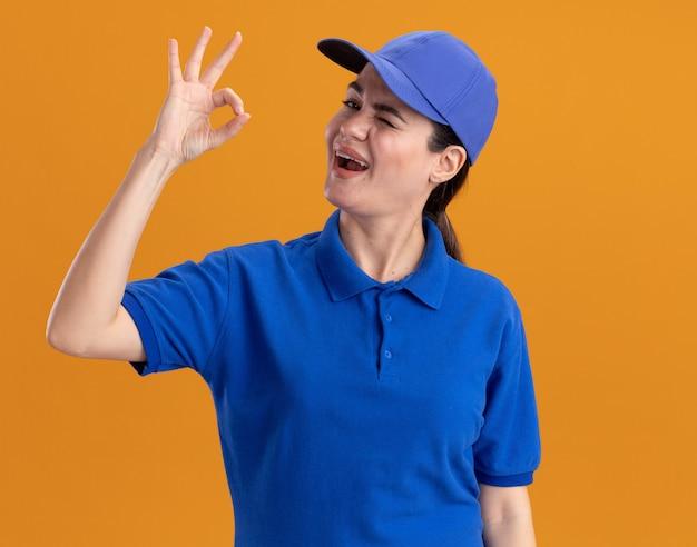 Zuversichtliche junge lieferfrau in uniform und mütze, die nach vorne zwinkert und ok zeichen auf oranger wand isoliert