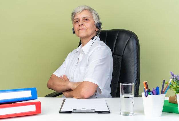 Zuversichtliche kaukasische call-center-betreiberin auf kopfhörern, die am schreibtisch mit bürowerkzeugen sitzen, die ihre arme einzeln auf grüner wand verschränken