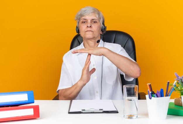 Zuversichtliche kaukasische call-center-betreiberin auf kopfhörern, die am schreibtisch mit bürowerkzeugen sitzen und ein time-out-zeichen einzeln auf oranger wand gestikulieren