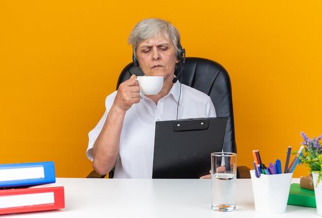 Zuversichtliche kaukasische callcenter-betreiberin auf kopfhörern, die am schreibtisch mit bürowerkzeugen sitzen, die tasse halten und die zwischenablage betrachten