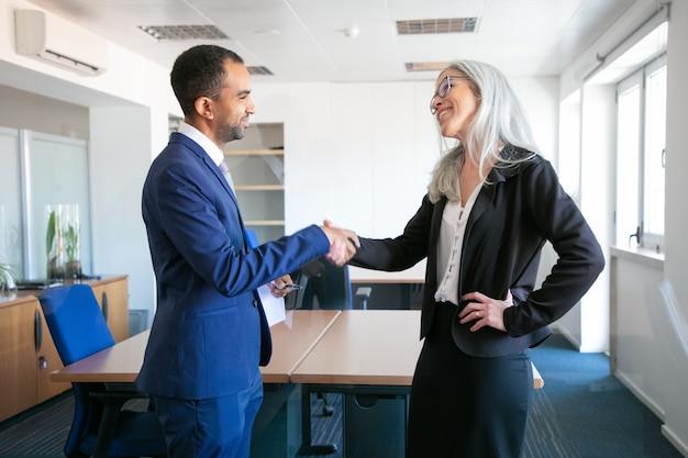 Zuversichtliche partner händeschütteln oder begrüßen im besprechungsraum. erfolgreicher content-geschäftsmann und professioneller grauhaariger manager, der den vertrag abschließt. teamwork-, geschäfts- und partnerschaftskonzept