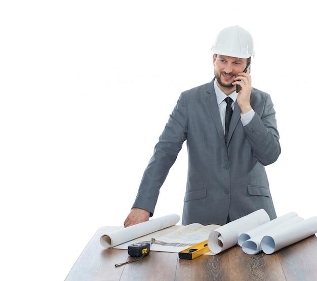 Zuversichtlicher architekt, der architekturplan des gebäudes liest, am arbeitsplatz, nahe am tisch stehend
