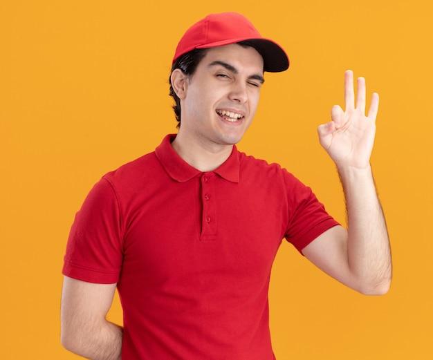 Zuversichtlicher junger kaukasischer liefermann in blauer uniform und mütze, der die hand hinter dem rücken hält, zwinkert und das ok-zeichen isoliert auf der orangefarbenen wand macht