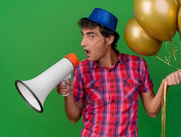 Zuversichtlicher kaukasischer parteimann mittleren alters, der partyhut hält, der ballons hält, die durch sprecher sprechen, der kamera lokalisiert auf grünem hintergrund betrachtet