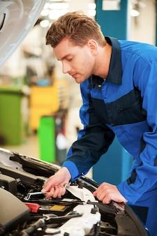 Zuversichtlicher mechaniker bei der arbeit. konzentrierter junger mann in uniform, der auto repariert, während er in der werkstatt steht