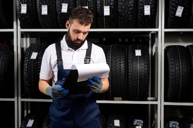 Zuversichtlicher mechanikermann, der eigenschaften des reifens im autowerkstatt prüft, papier betrachtend betrachtet, blaue uniform tragend