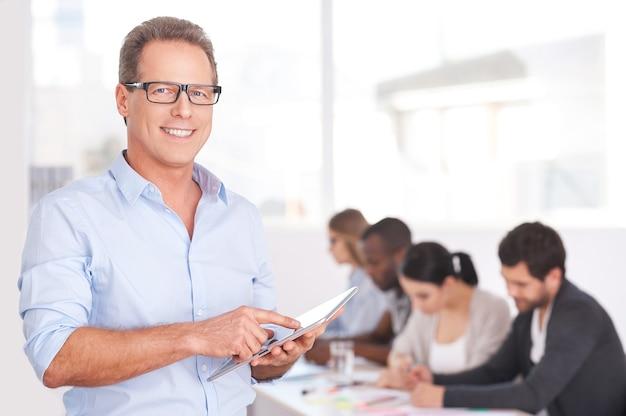 Zuversichtlicher teamleiter. selbstbewusster junger mann mit brille, der an einem digitalen tablet arbeitet und lächelt, während die leute am hintergrund arbeiten