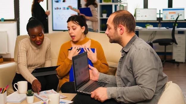 Zuversichtlicher unternehmensleiter, der verschiedenen teamkollegen, die auf der couch im start-up-büro sitzen, arbeitsaufgaben gibt. multiethnisches team diskutiert projektideen beim brainstorming-meeting mit digitalen geräten