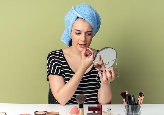 Zuversichtliches blick auf den spiegel junges schönes mädchen sitzt am tisch mit make-up-tools, die haare in ein handtuch gewickelt haben und lippenstift einzeln auf olivgrüner wand auftragen