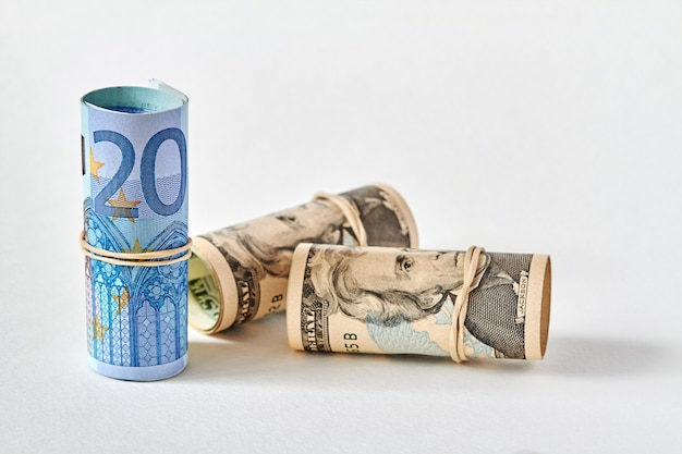 Zwanzig-euro-scheine, aufgerollt als tubulus, stehen auf dem hintergrund von zwanzig-dollar-scheinen. konzept der euro-überlegenheit gegenüber dem dollar. nahaufnahme, selektiver fokus