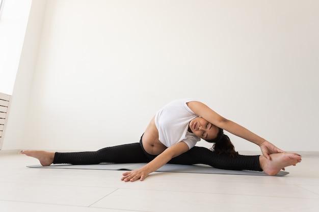 Zweckmäßige schwangere frau trainiert während des yoga-kurses und entspannt sich beim sitzen auf einer matte