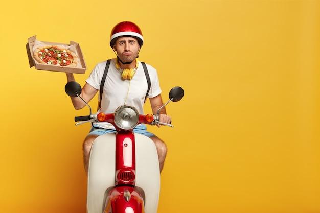 Zweckmäßiger hübscher männlicher fahrer auf roller mit rotem helm, der pizza liefert