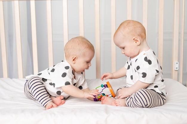 Zwei 8 monate alte zwillingsbabys spielen in der krippe, frühe entwicklung von kindern bis zu einem jahr