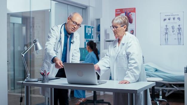 Zwei ältere erfahrene ärzte entscheiden über die behandlung des patienten, während die krankenschwester im hintergrund arbeitet. ältere authentische ärzte in der modernen privaten krankenhausklinikraum-gesundheitssystemmedizin und t