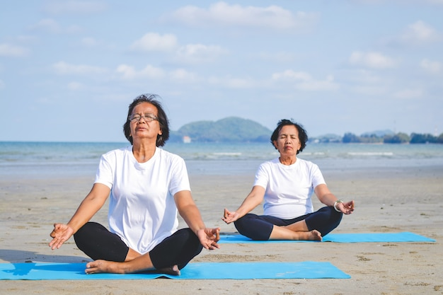 Zwei ältere frauen, die am strand durch das meer trainieren, yoga sitzend und tuend
