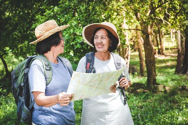 Zwei ältere frauen, die einen rucksack tragen und eine karte tragen. das konzept der senioren, die die natur reisen